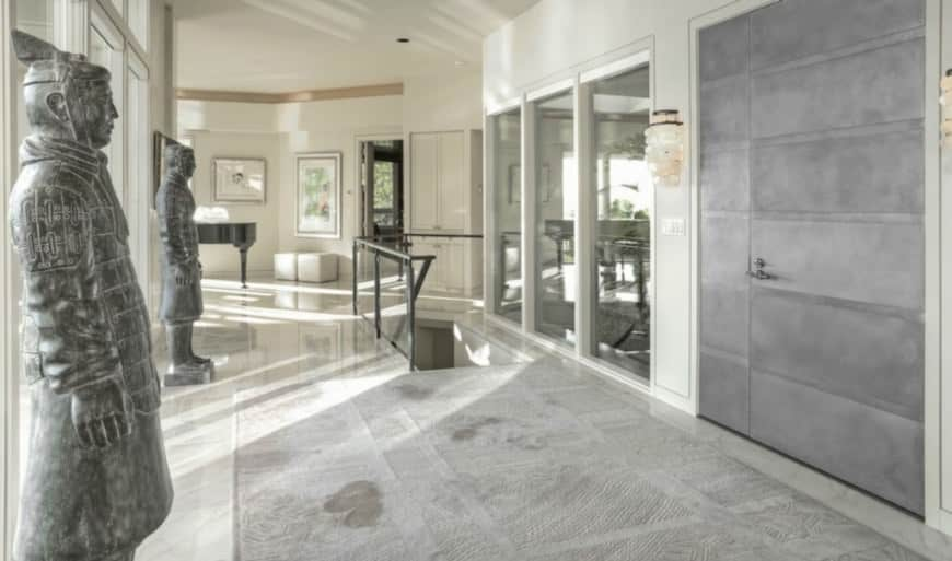Large foyer with a stylish rug set on a smooth tiles flooring. White walls and glass windows look so glamorous with each other.