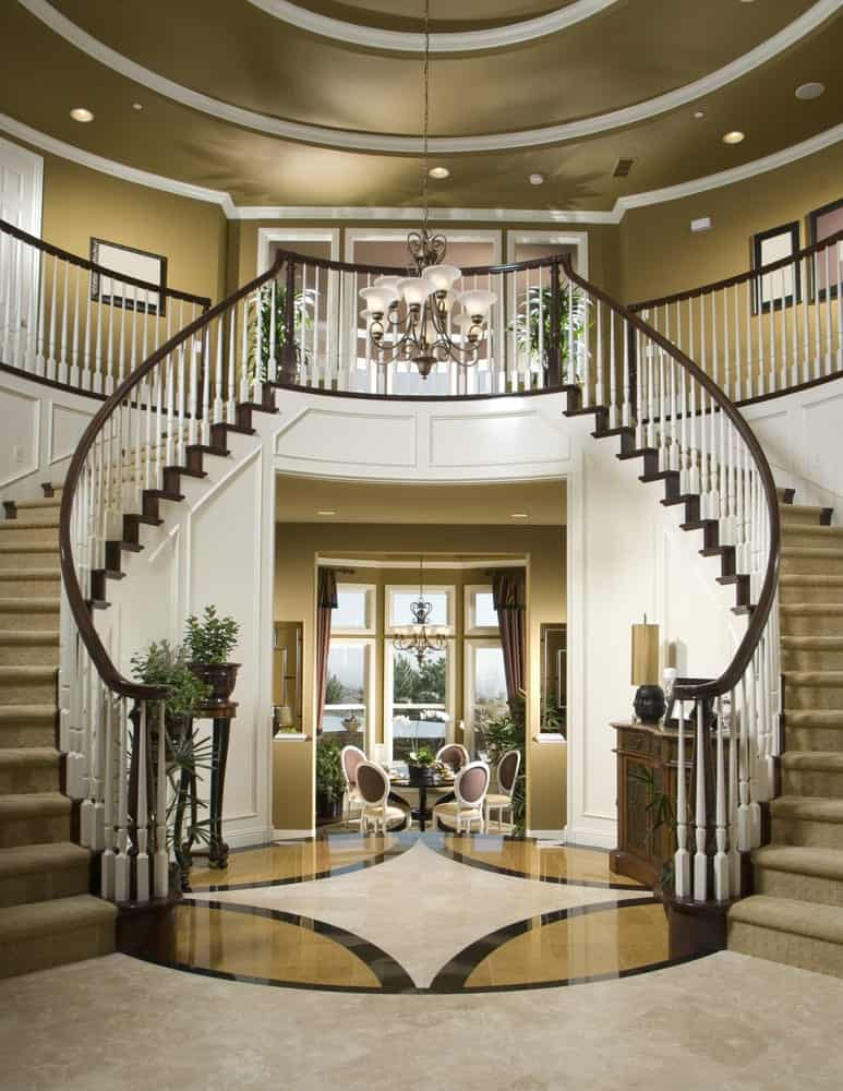 A large foyer featuring a beautiful flooring, staircase, walls and ceiling. The pendant and recessed lights look perfect together.