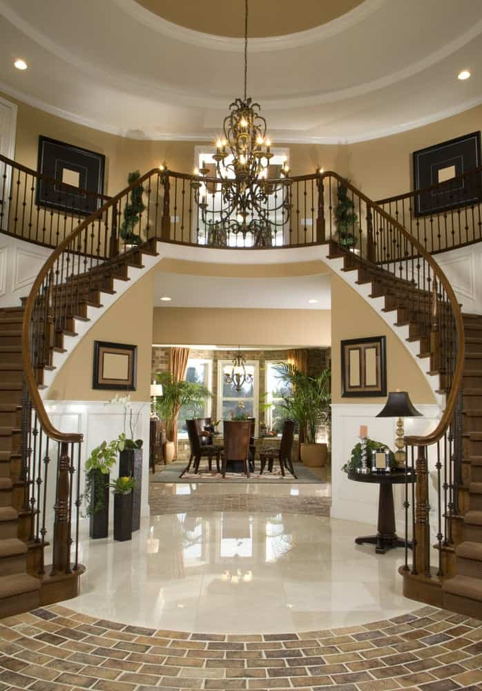 A large foyer full of elegance. The shiny tiles flooring reflects the light coming from the grand chandelier. The staircase looks magnificent.