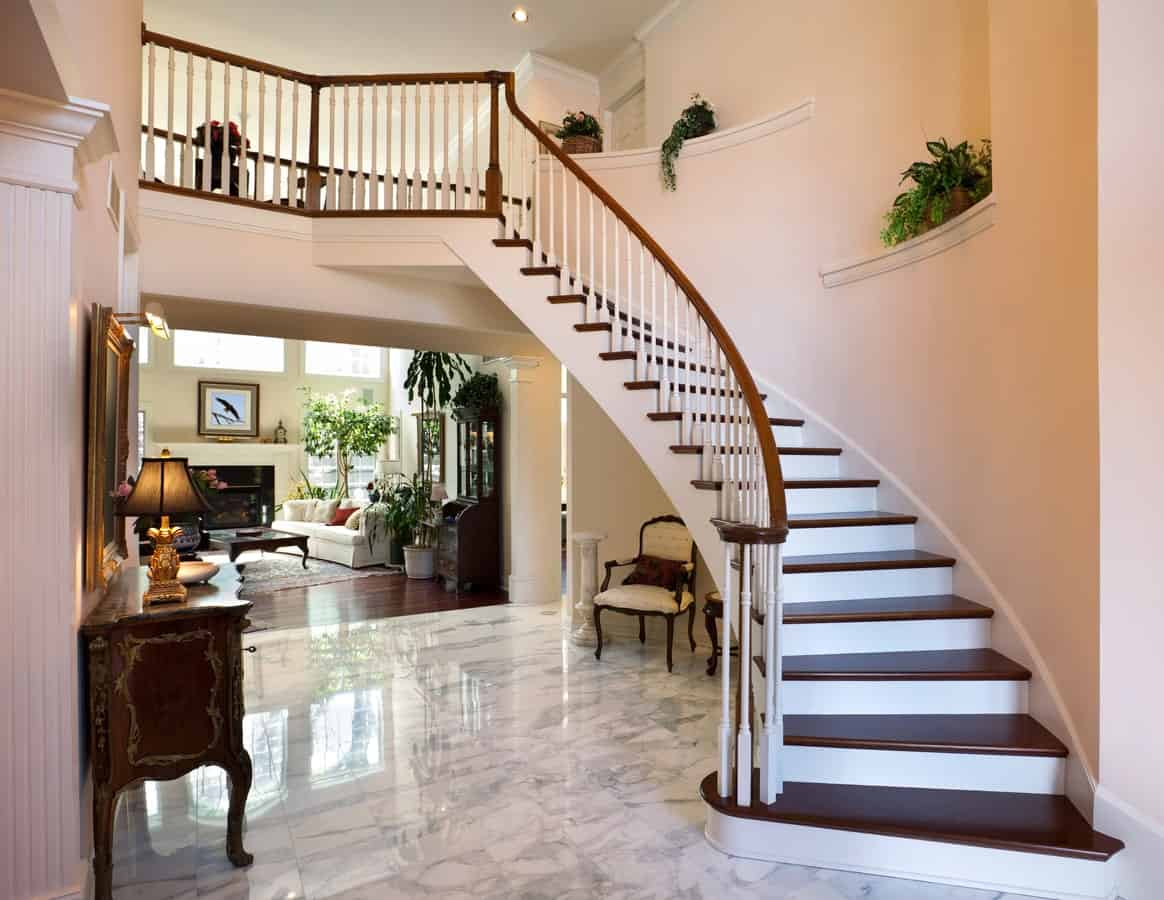 This foyer offers a sparking tiles flooring leading to the beautiful staircase. Plants are everywhere on the home giving an additional color.