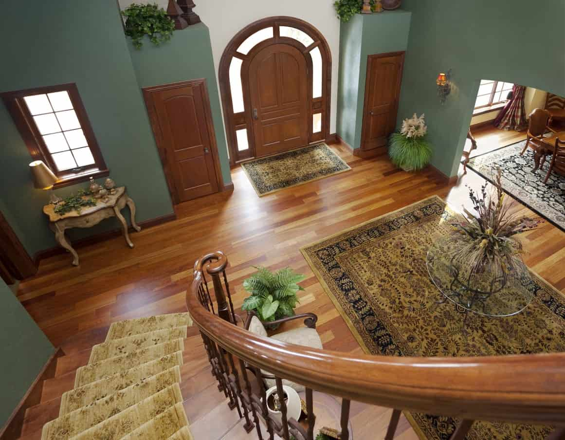 This large foyer boasts a beautiful combination of green and brown colors. The rugs look so elegant.