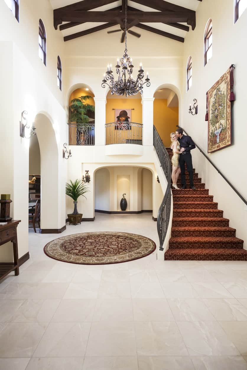 This large foyer looks so magnificent. The tiles flooring fits perfectly well with the rug and staircase's steps. The chandelier set on a stylish ceiling is definitely an eye-catcher.
