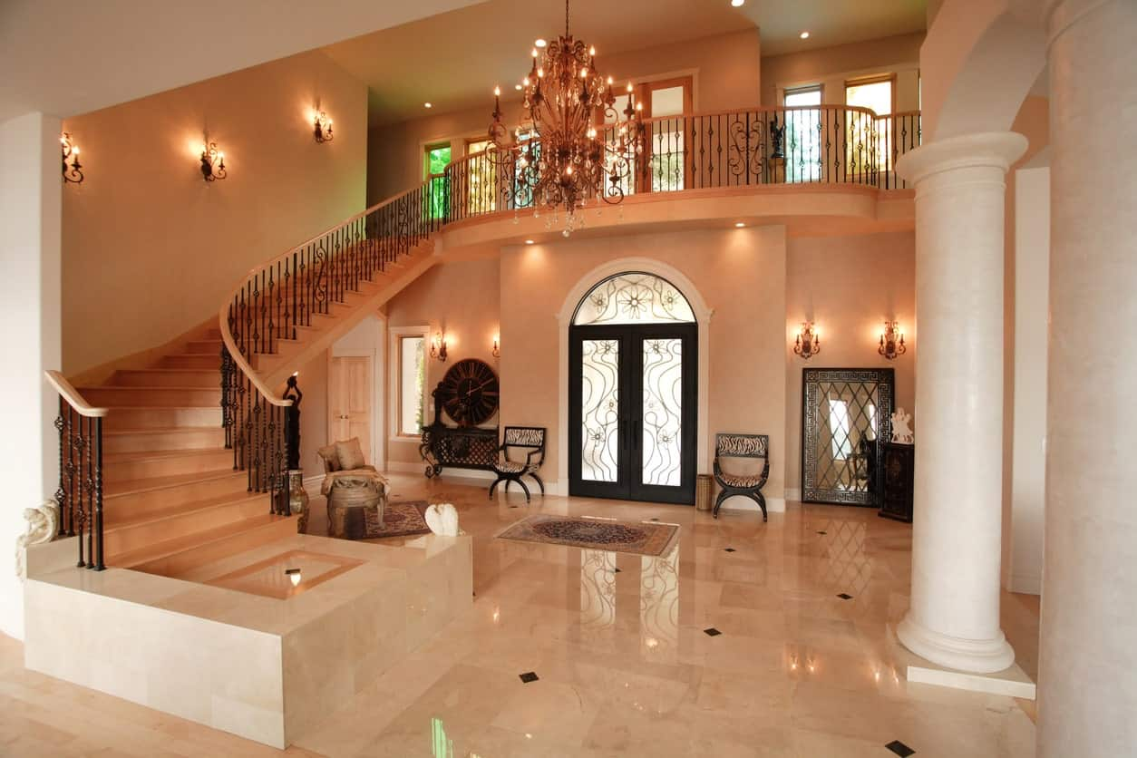 A very elegant large foyer featuring bright lights from the grand chandelier and classy wall lighting. The tiles flooring is sparkling from the brightness.