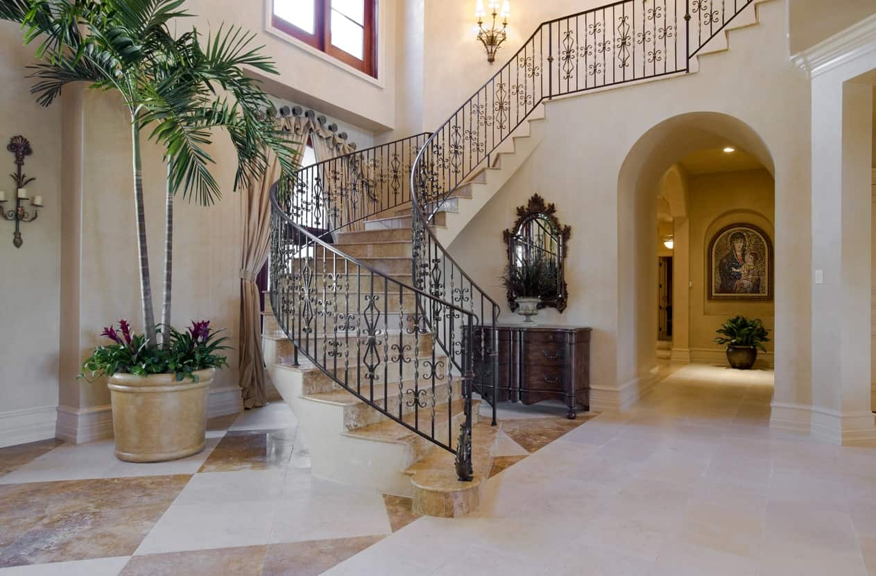 A large foyer featuring classy tiles flooring and staircase. The wall lighting looks so beautiful while the indoor plants add beauty to the home's entry.