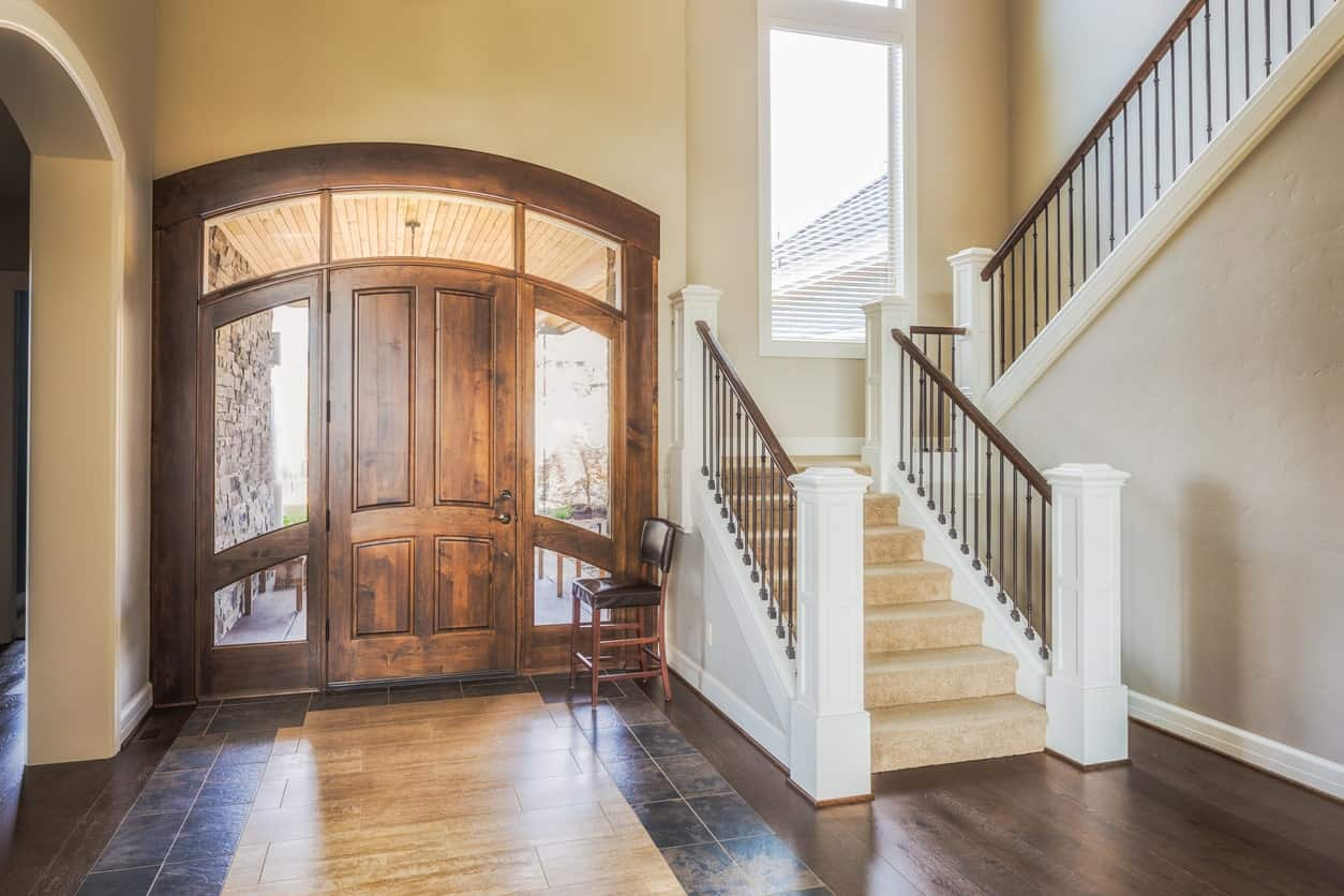 This simple yet classy large foyer features a stylish combination of hardwood and tiles flooring. The walls fits perfectly with the foyer's door style.