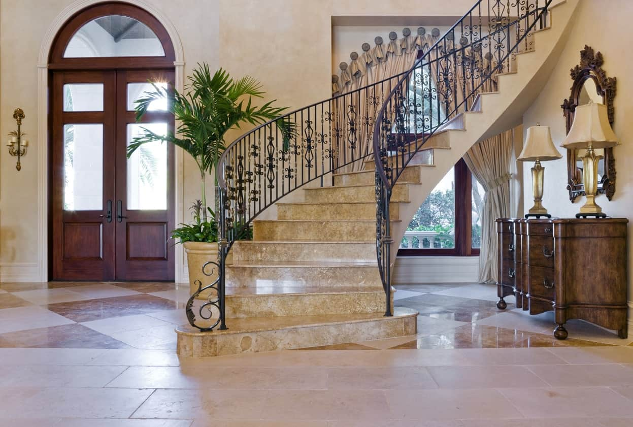 This large foyer boasts a stunning staircase featuring marble steps with iron railings. The curtains are also very beautiful.
