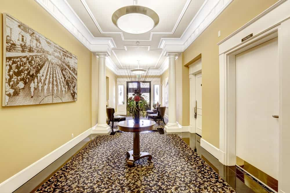 This very stylish large foyer features an elegant rug, wall decors and a ceiling. The foyer's style looks so perfect in every aspects.