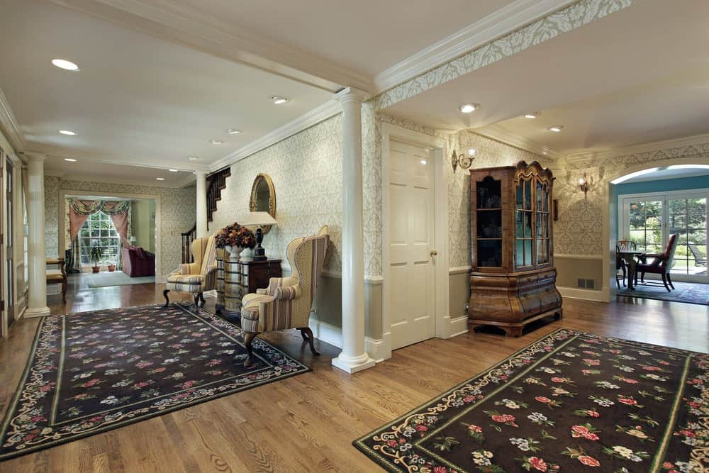 This large foyer looks so elegant with its walls and rugs. The recessed ceiling lights scattered light up the hallway.
