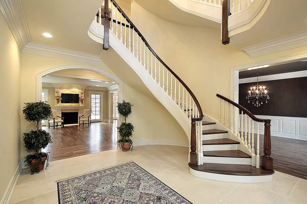 This bright large foyer features tiles flooring topped by a classy rug. The staircase's steps and railings are a perfect match.