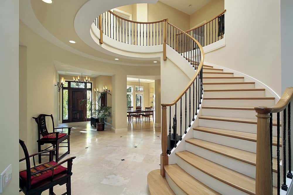 This classy large foyer features a gorgeous staircase with vinyl steps and iron railings. The recessed ceiling lights are perfectly and beautifully placed.