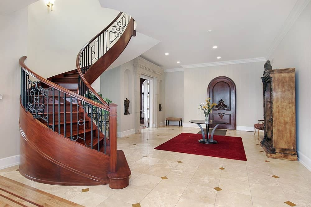 Large foyer with tiles flooring topped by a red elegant rug lighted by recessed ceiling lights. The staircase looks magnificent.