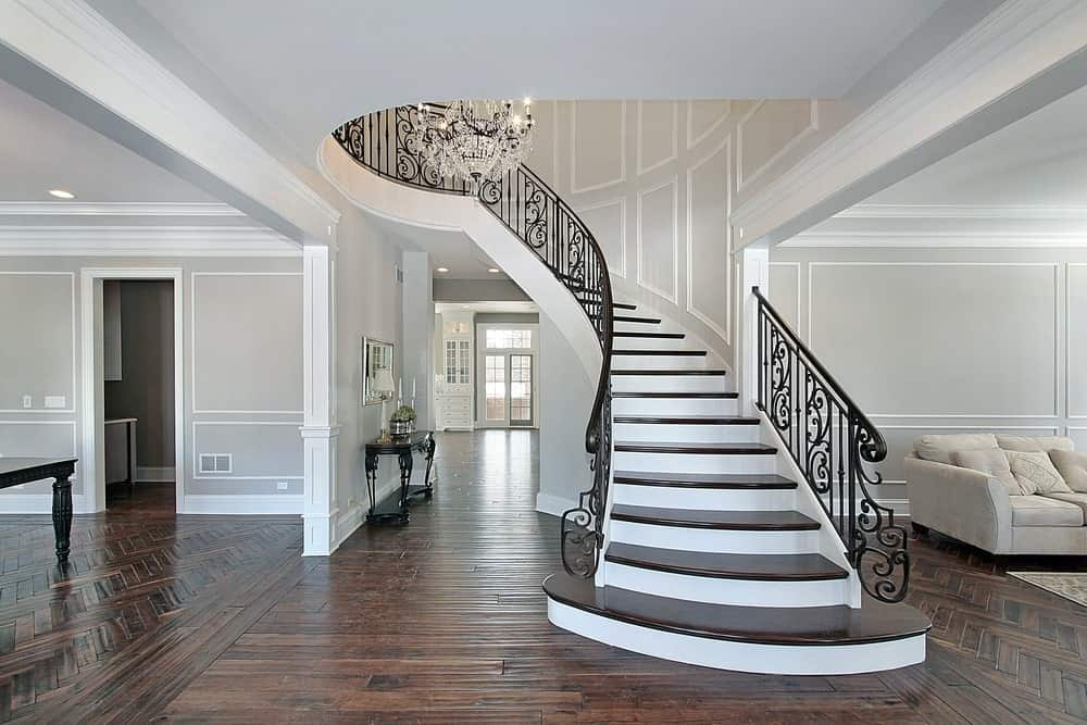 This bright foyer features a hardwood flooring and smooth dark brown staircase steps with iron railings.
