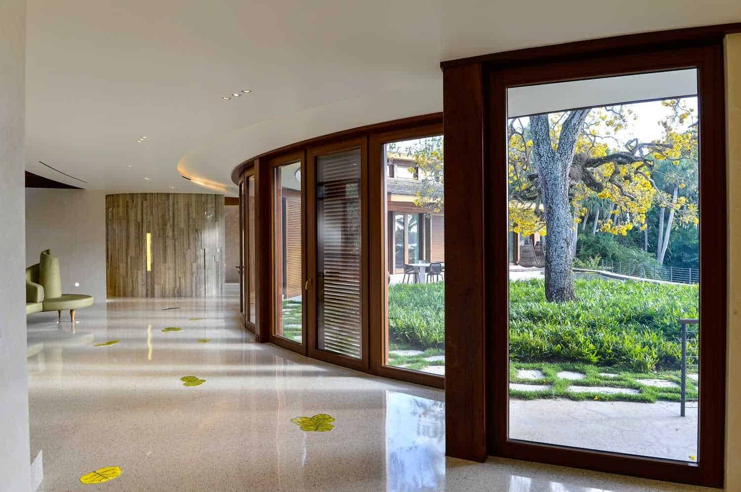 This large foyer features a smooth flooring with designs and glass doors and windows overlooking the outdoor space.