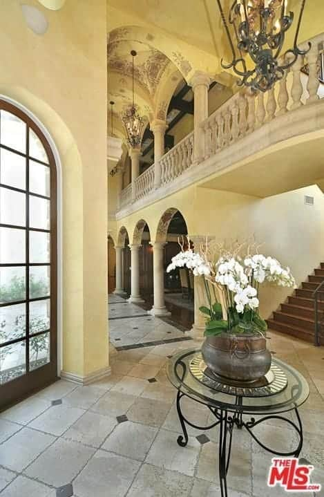 Large Mediterranean foyer featuring tiles flooring and a beautiful ceiling lighted by elegant pendant lights.