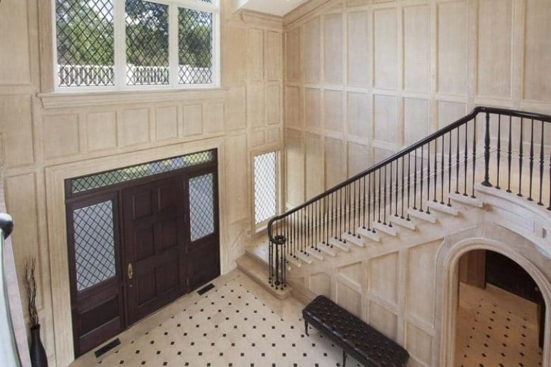 Top view of a large foyer featuring white walls and flooring and a large door. The staircase looks classy.