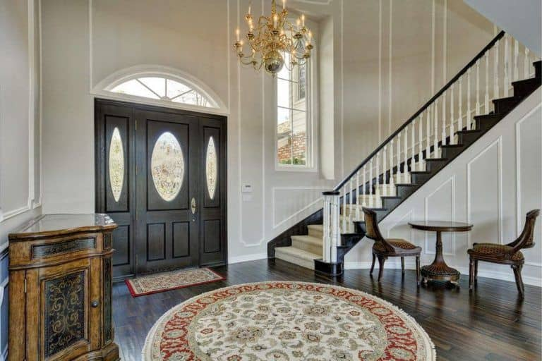 Large foyer featuring white walls and hardwood flooring topped by a round rug and is lighted by an elegant chandelier.