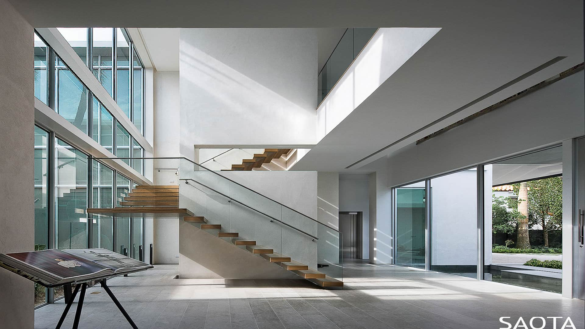Large modern foyer with white walls and glass walls and windows overlooking the outdoor space.