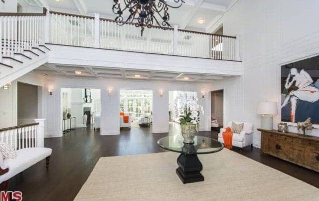 This large foyer features a hardwood flooring topped by a rug along with white walls lighted by elegant chandelier and wall lighting.