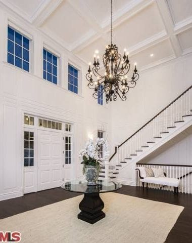 Large foyer with a hardwood flooring and a rug. The white walls are perfect with the chandelier.