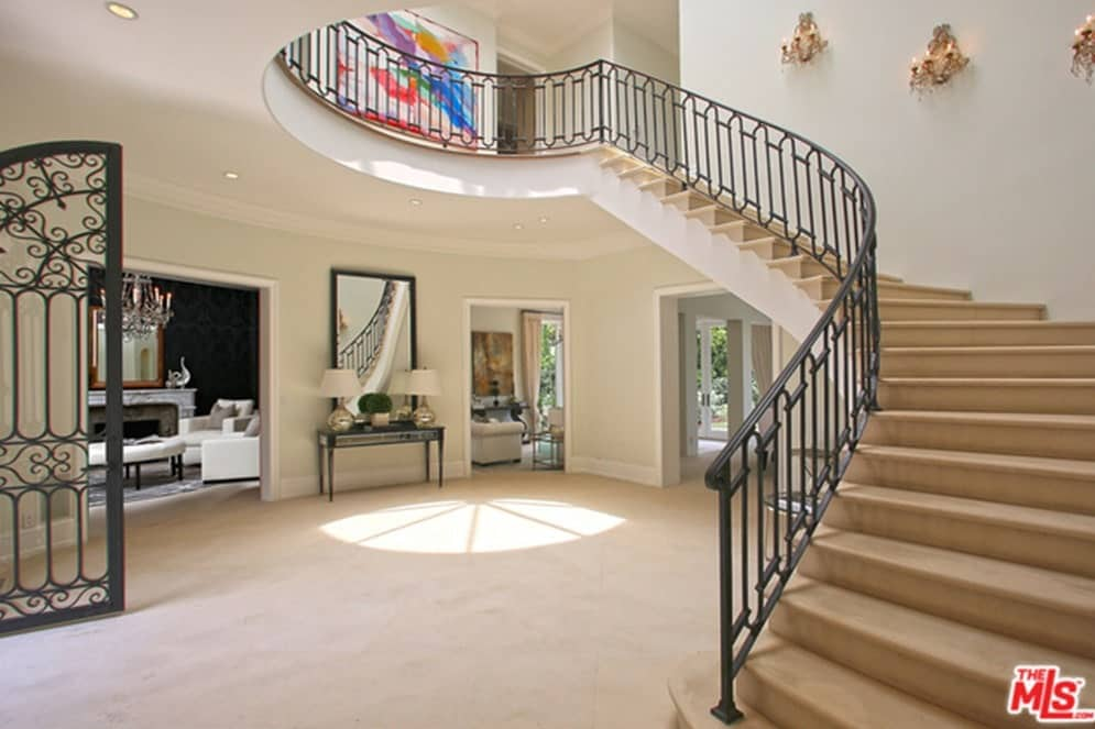 Large foyer featuring a carpet flooring and white walls. The staircase looks so good as well, lighted by a set of wall lighting.