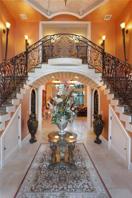 This large foyer boasts an elegant look with its flooring, walls, ceiling, lighting and staircase.