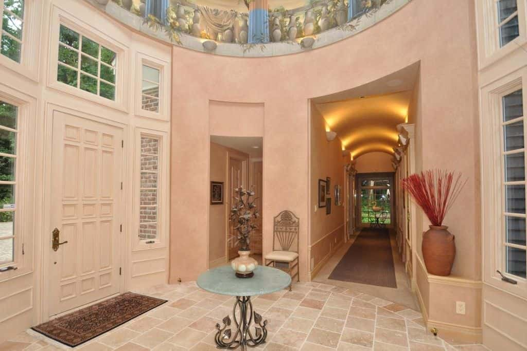 Large bright foyer featuring tiles flooring and a circular main hall. The hallway is lighted by stunning set of wall lighting.