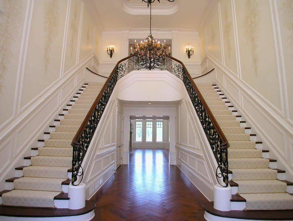 Large foyer with amazing staircases and hardwood flooring. The staircases' steps are topped by elegant rugs. The area is lighted by a grand chandelier.