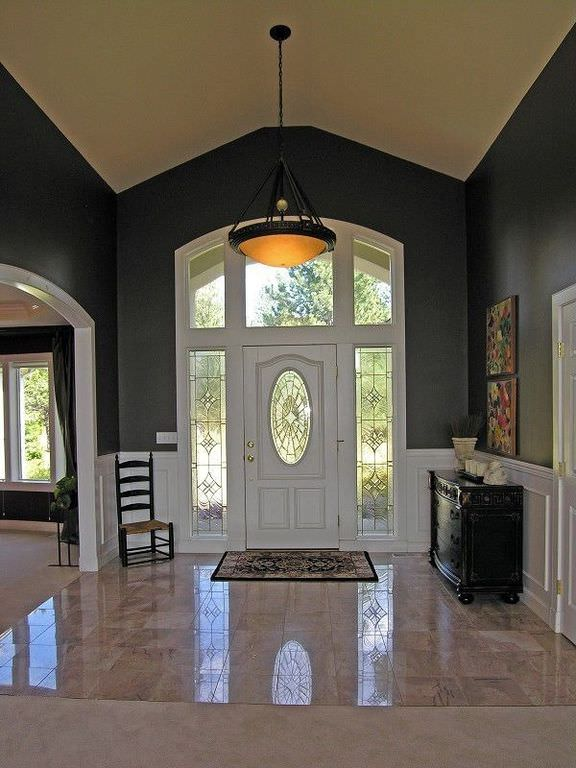 This large foyer features a black and white walls and has a classy pendant light hanging from the vaulted ceiling.
