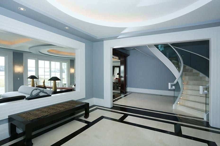 Large modern foyer with gray walls and stylish flooring along with the elegant staircase. The foyer's style looks perfect together with the home's style.