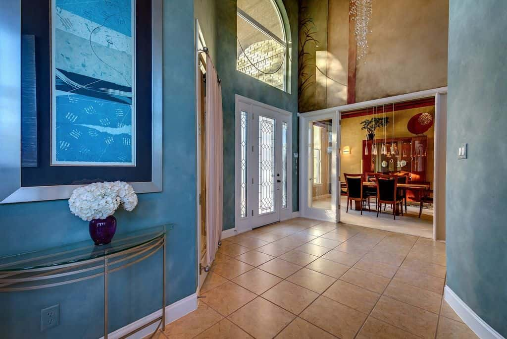 This large foyer feature blue walls and tiles flooring. The high ceiling offers a stunning pendant light.