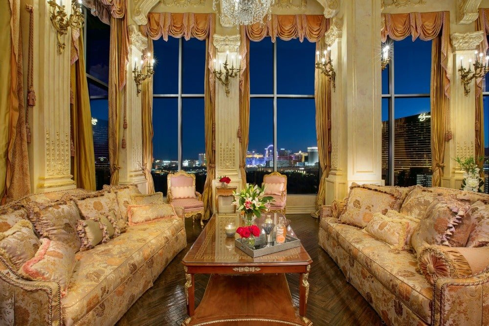 A focused look at the formal living's luxurious sofa set lighted by elegant wall lights in between tall windows. Image courtesy of Toptenrealestatedeals.com.