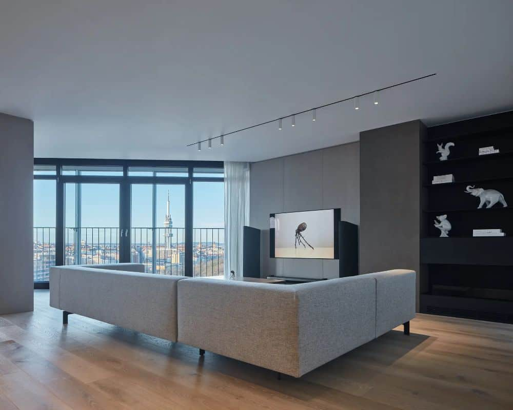 This is an interior view of the apartment's minimalist living room with a large sectional sofa across from the TV. These are then complemented by the glass windows that have panoramic views outside. This was designed by Barbora Léblová Interiors & Architecture.