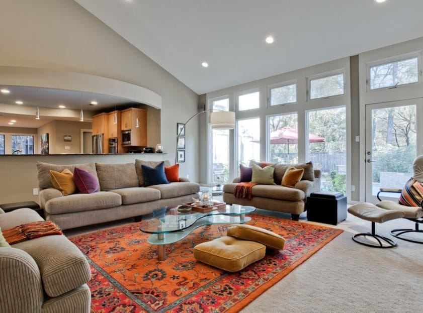 This gorgeous living room is proof that you don't have to splurge on extra luxurious furniture to get the living room of your dreams. A large, bright carpet in the center surrounded by vivid colorful cushions/sofas will do the trick.