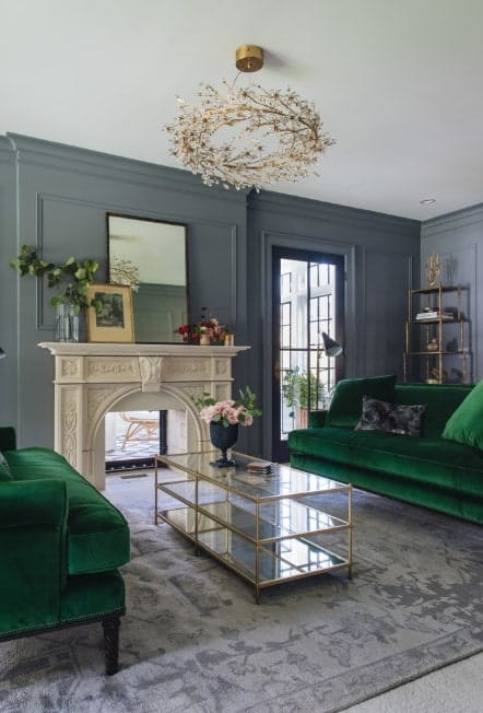 The alluring green sofa, dark gray walls and a carpet shows how two poles-apart shades can come together and work like magic. Note that both sofas and carpet boast velvety texture, giving the room a luxurious aura.