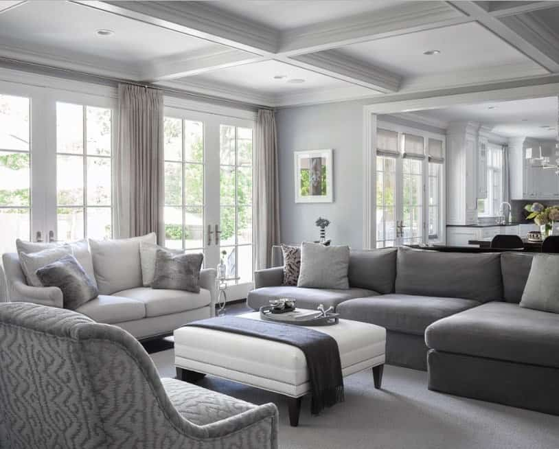 A formal living room featuring a modish set of gray seats on top of the gray carpet flooring. The coffered ceiling looks handsome.