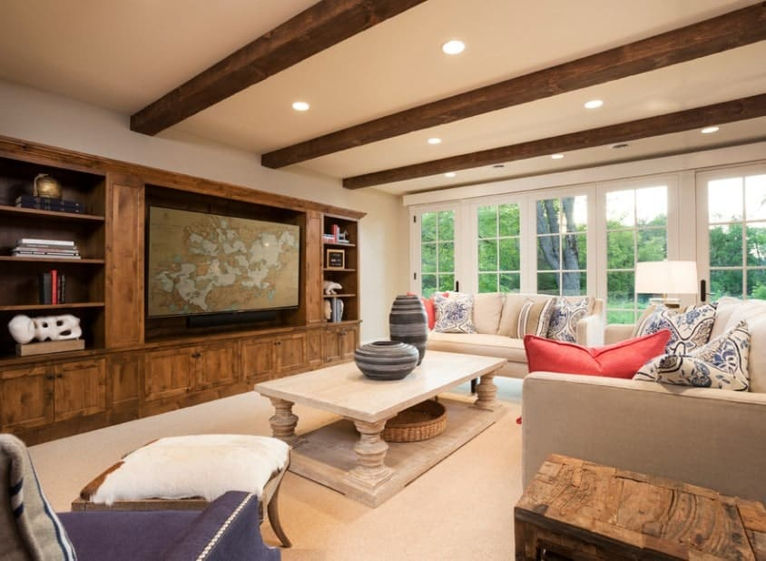 This formal living room boasts elegant rustic shelving and drawers along with the carpet flooring and ceiling with beams.