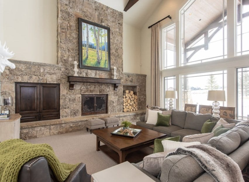 A formal living room boasting a high vaulted ceiling and a stunning large fireplace along with cozy sofa set and carpet flooring.