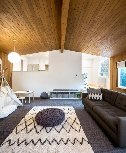 A large living room with stylish brown carpet flooring matching the brown couch. The vaulted wooden ceiling is just charming as well.