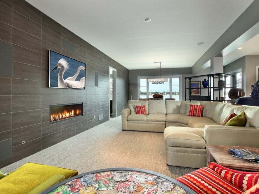 Large living room featuring a widescreen TV on the wall. Below is the modish fireplace keeping the place warm. The room also offers a cozy sofa set on top of the carpet flooring.