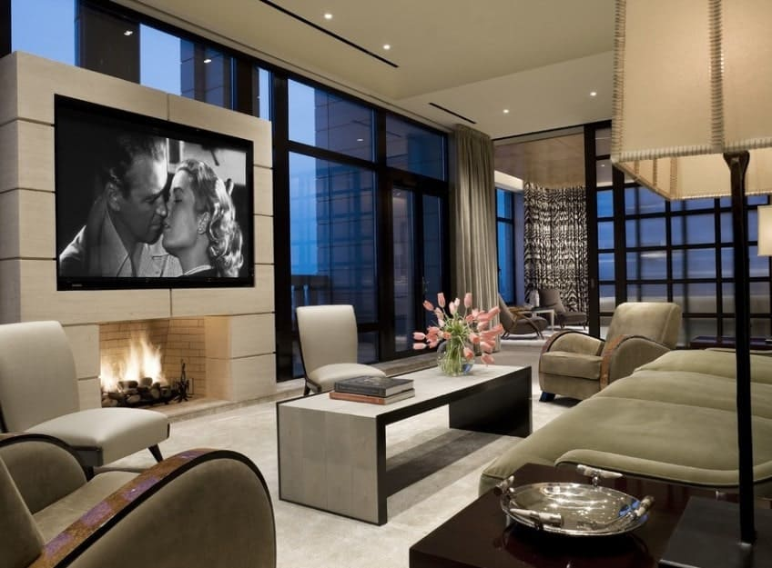 A modern living room featuring a stunning TV set up on top of the fireplace. The room offers cozy seats set on the white carpet flooring.