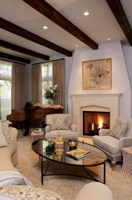 A classy living room with an elegant piano on the corner. The room features a fireplace and classy set of seats set on the carpet flooring.