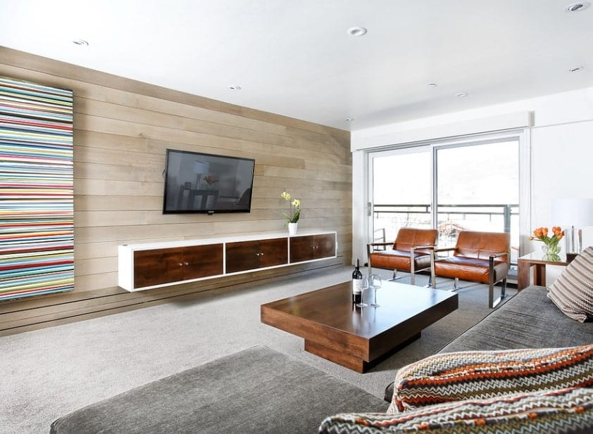 A large formal living room with modish TV and counter along with a stylish center table near the gray sofa set on top of the white carpet flooring.