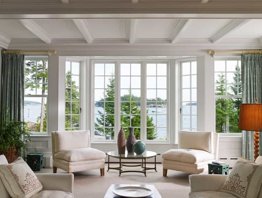 A classy living room featuring French windows and a lovely set of seats set on the carpet flooring. The coffered ceiling adds elegance to the room.