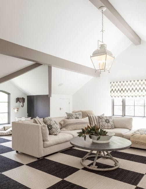 A bright living room with white walls and black and white checker carpet flooring.