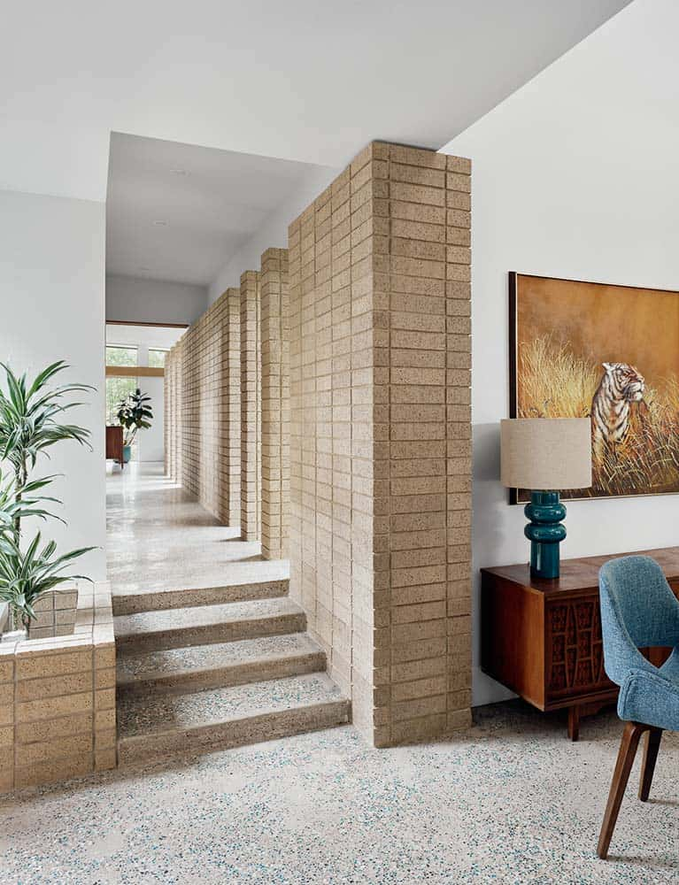 Upon entry into the house, you are welcomed by this foyer that has an abundance of natural lights, gray flooring and brick walls that match with the planter on the side with a small tropical plant. This also ha a view of the waist-high wooden cabinet and wall artwork on the side.