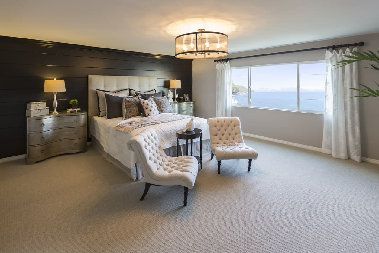 A candelabra chandelier with drum shade spotlights the tufted armless chairs at the foot of the bed with a side table in-between. The room's neutral tones make it look relaxing and direct the eyes to the windows and outwards with its spectacular views of the water.