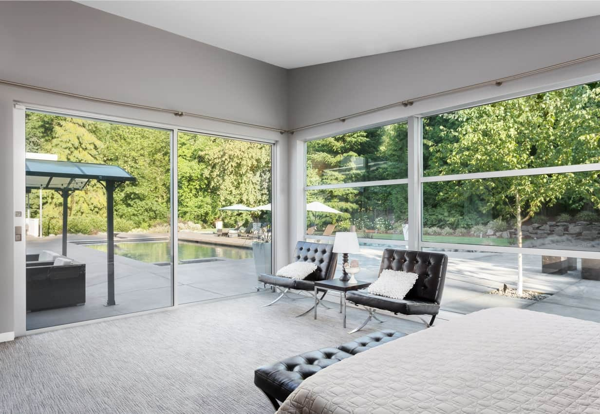 This modern bedroom manages to fuse Zen with its modern look by incorporating the green outdoors and concrete patio with a pool through its glass walls. The stylish black tufted chairs serve not just as sitting areas but are also the perfect pieces to complete and complement the look.