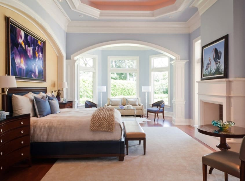 The tall tray ceiling with pronounced crown moldings, arches, and columns flaunts this master bedroom's massive space and makes the sitting area by the bay windows look smaller. The unexpected blue paint on the walls gives the room a friendlier look.