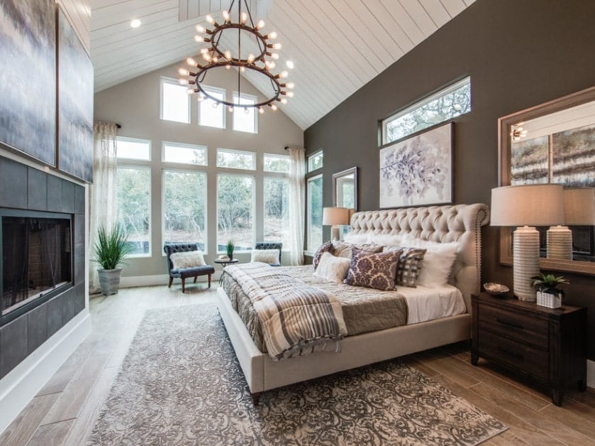 A white 2-story pitched pallet ceiling with the 2-tiered chandelier is offset with the black accent wall and the large fireplace facing the bed. Large windows let in plenty of natural lighting for a bright and airy look while the pair of tufted chairs by the window looks small.