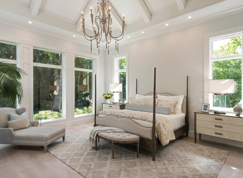 This modern master bedroom feels luxurious with its candelabra chandelier, four poster bed, and large windows that make up for the bare white walls. The chaise lounge and tufted bench at the foot of the bed and standing on the gray rug add a subtle glamor to the room.